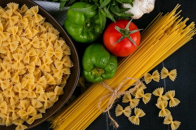 Вид сверху сырых спагетти с сырой пастой в миске с помидорами, чесноком и болгарским перцем на черной поверхности