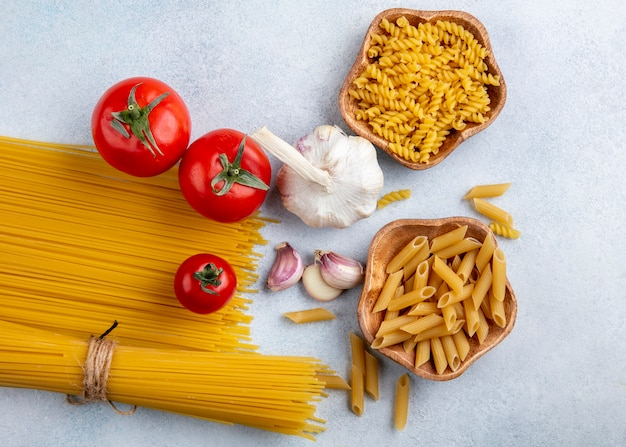 Вид сверху сырых спагетти с сырой пастой в мисках с чесноком и помидорами на серой поверхности