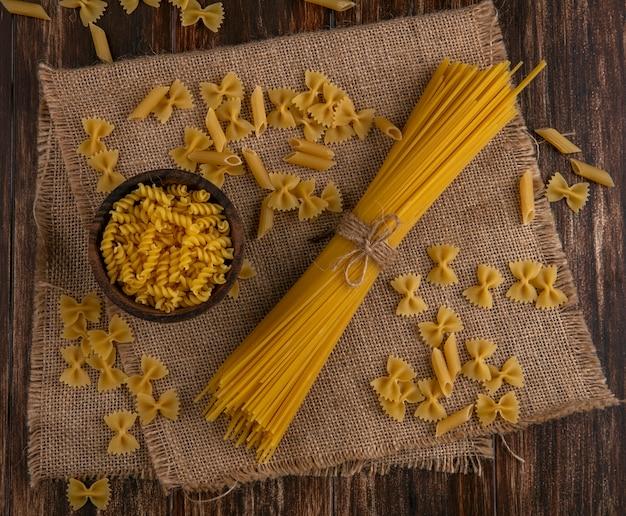 Вид сверху сырых спагетти с сырой пастой на бежевой салфетке