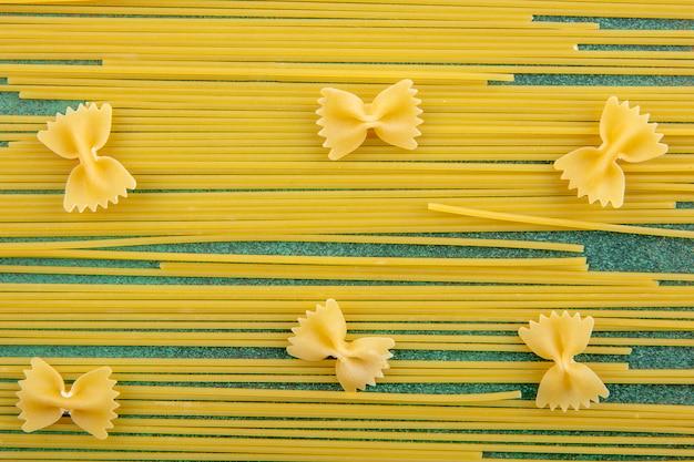 Вид сверху сырых спагетти с сырой пастой на зеленой поверхности