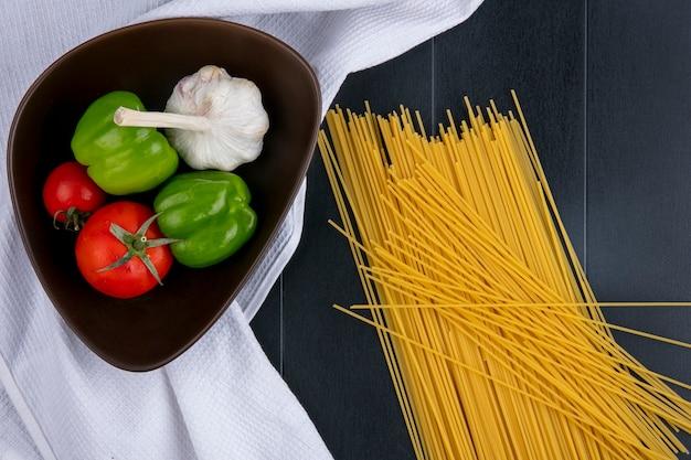 黒い表面に白いタオルの上にボウルにトマトニンニクとピーマンの生スパゲッティのトップビュー