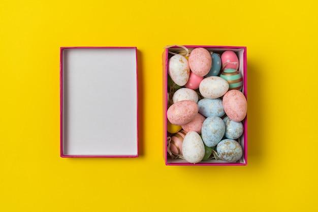 Вид сверху прямоугольной коробки с пасхальными яйцами на желтом фоне. разноцветные праздничные яйца.