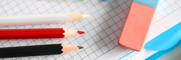 赤と黒の鉛筆の平面図です。シルバーペンと消しゴム。デスクトップ上のカラフルなブックマーク。空のノートブックシート。メモと創造的なアイデアのための紙。オフィス文具コンセプト