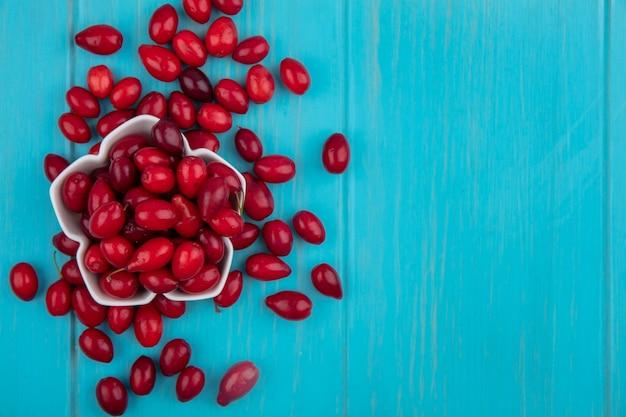 コピースペースと青い木製の背景の上の白いボウルに赤と新鮮なコーネルフルーツの上面図