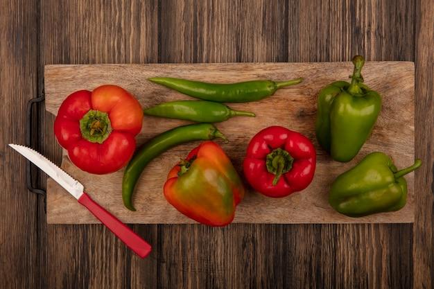 Вид сверху красного и зеленого перца на деревянной кухонной доске с ножом на деревянной поверхности