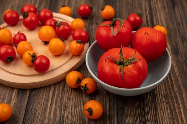 木製の壁のボウルに大きなサイズのトマトと木製のキッチンボードで分離された赤とオレンジのチェリートマトの上面図