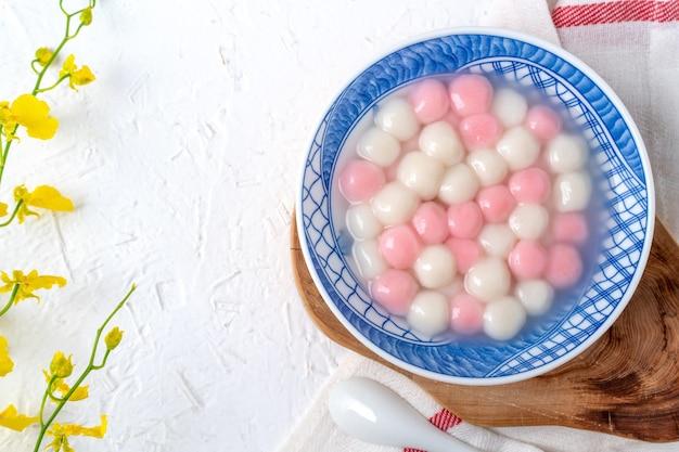 동지 축제 음식에 대 한 흰색 바탕에 파란색 그릇에 빨간색과 흰색 탕 위안 (탕 위안, 찹쌀 만 두 공)의 상위 뷰.