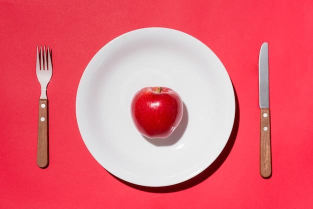 Вид сверху красного яблока на белой тарелке с ножом и вилкой на красном фоне