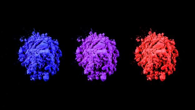 검정 배경 위에 행으로 배열 된 빨강, 파랑 및 자주색 Holi 색상의 상위 뷰 무료 사진