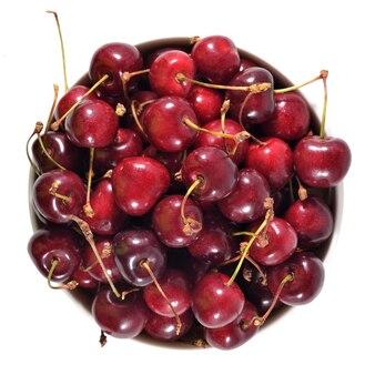 Вид сверху красной вишни в белой миске на белом фоне
