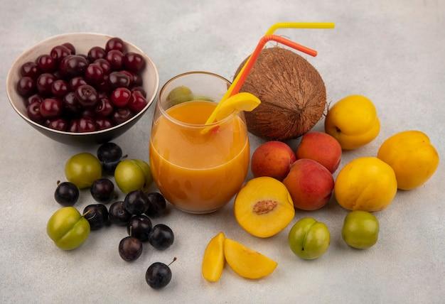 Вид сверху красной вишни на миске со свежим персиковым соком со свежими фруктами, такими как персики, зеленые алычи, изолированные на белом фоне