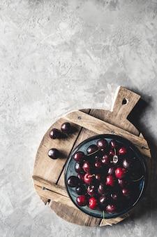 Вид сверху красной вишни на миске с ломтиками персиков на деревянной кухонной доске с ножом на бетонном фоне
