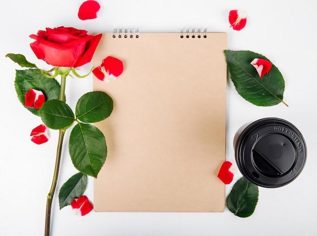 白い背景の上のスケッチブックと一杯のコーヒーと赤い色のバラのトップビュー