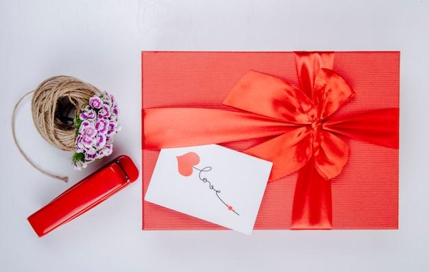 Вид сверху красной подарочной коробке, перевязанной бантом и небольшой открыткой, шаром из веревки с турецкой гвоздикой, цветком красный степлер на белом фоне