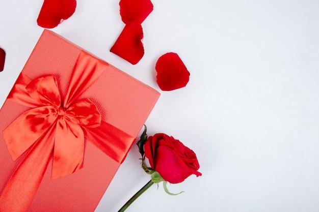 Вид сверху красной подарочной коробке с бантом и красной розой и лепестками на белом фоне