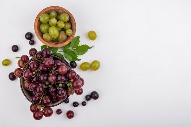 Вид сверху красного винограда и белых виноградных ягод в мисках с виноградными ягодами и листьями на белом фоне с копией пространства