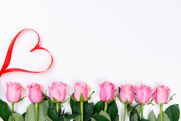 赤いハートと白い背景の上のピンクのバラのフレームの上面図。バレンタインデーのコンセプト。