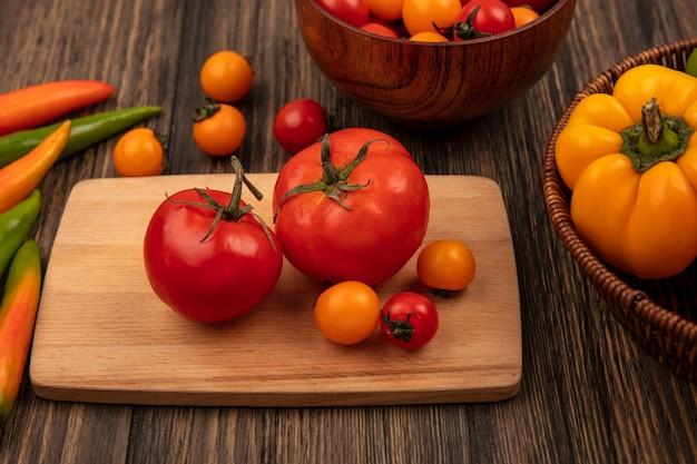 Вид сверху красных помидоров большого размера на деревянной кухонной доске с помидорами черри на деревянной миске и болгарским перцем на ведре на деревянной поверхности