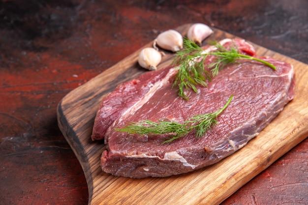 Вид сверху красного мяса на деревянной разделочной доске и зеленого чеснока на темном фоне