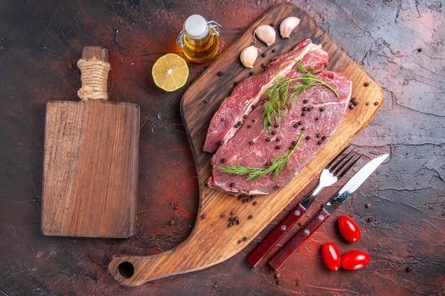 Вид сверху красного мяса на деревянной разделочной доске и чеснока, зеленого перца, вилки и ножа на темном фоне