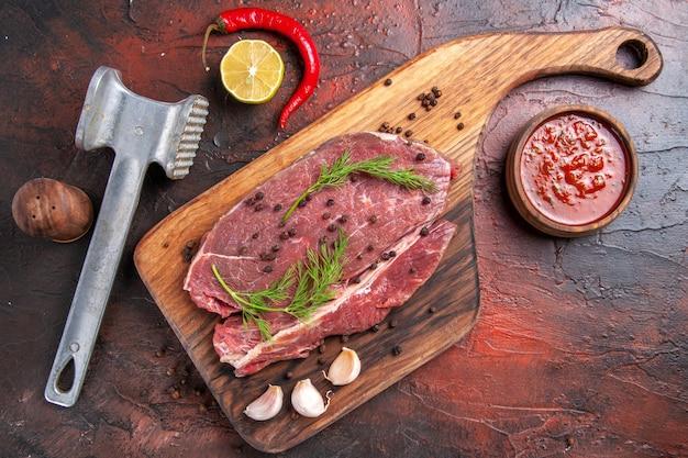 Вид сверху красного мяса на деревянной разделочной доске и чеснока, вилки и ножа для бутылки с маслом зеленого перца на темном фоне кадра