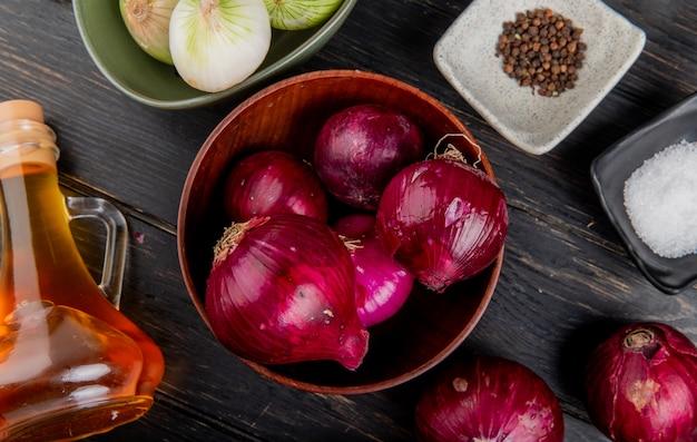 白い玉ねぎのボウルとボウルに赤玉ねぎの平面図溶かしたバター黒胡椒塩の木製の背景