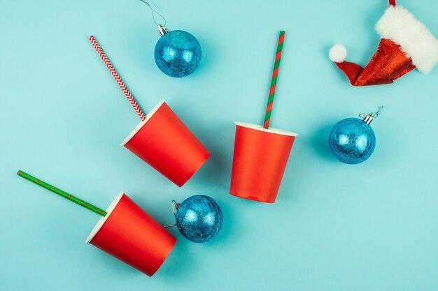 파란색 배경에 칵테일 빨대, 싸구려, 산타 모자가 있는 빨간 종이컵의 꼭대기. 휴일 디자인을 위한 축제 크리스마스 레이아웃