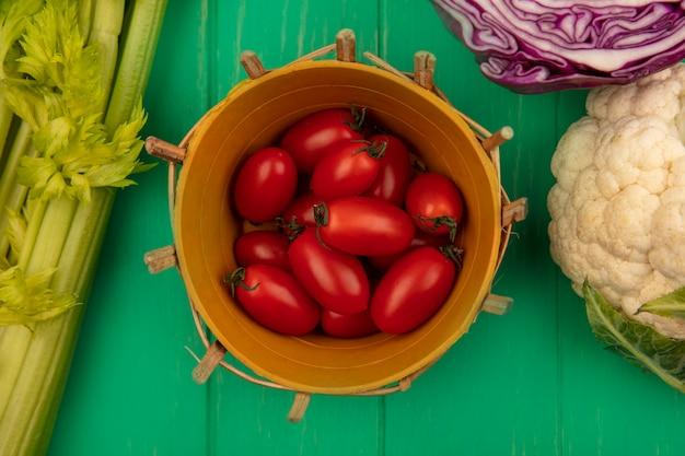 Вид сверху красных сливовых помидоров на ведре с фиолетовой цветной капустой и сельдереем, изолированными на зеленой деревянной стене