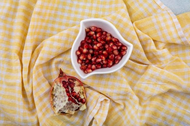 チェックの黄色のテーブルクロスの表面に半分ザクロと白いボウルに赤いザクロの種子のトップビュー