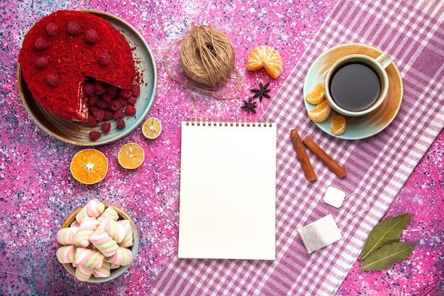 Вид сверху красного малинового торта с корицей, мандаринами и чаем на розовой поверхности