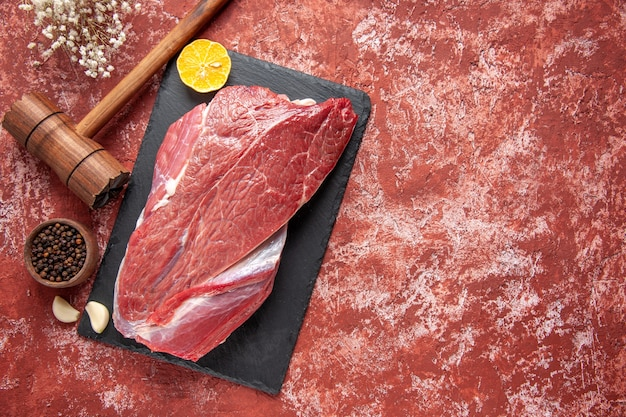 黒のボード上の赤い生の新鮮な肉レモンとパステルカラーの赤い背景の上の茶色の木製ハンマーペッパーの上面図