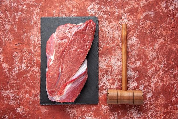 黒のボード上の赤い生の新鮮な肉とパステルカラーの赤い背景の上の茶色の木製ハンマーの上面図