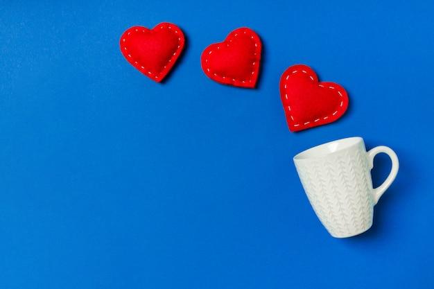カラフルな背景のカップからはねかける赤い繊維心の平面図です。幸せなバレンタインデーのコンセプト
