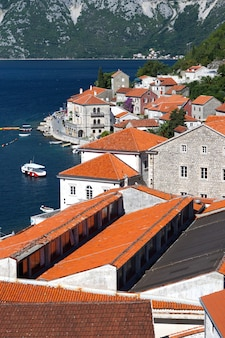 海岸沿いの町の赤い瓦屋根、石造りの家のある遊歩道、観光客の平面図