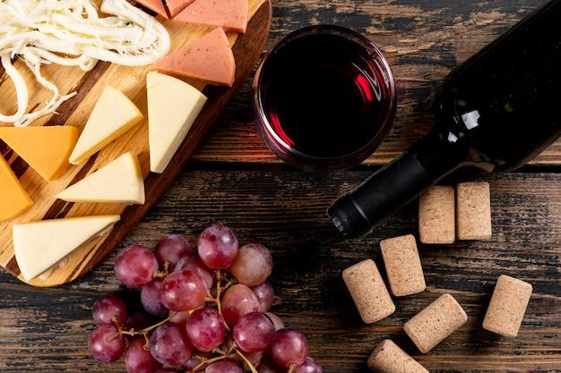 어두운 나무 가로 커팅 보드에 포도와 치즈와 레드 와인의 상위 뷰