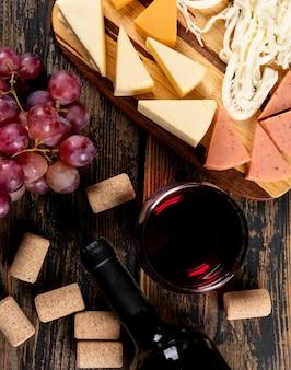 Взгляд сверху красного вина с виноградом и сыром на разделочной доске на темной деревянной вертикали