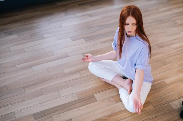 明るいオフィスルームで蓮のポーズで床に座って瞑想している赤毛の平和な若い女性の平面図です。