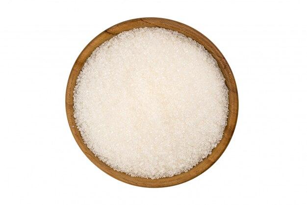 Взгляд сверху рафинированного сахарного песка в деревянном шаре на белой предпосылке.
