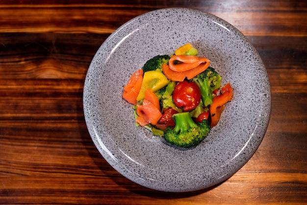 나무 카운터에 아름다운 회색 접시에 연어와 상쾌한 샐러드의 상위 뷰