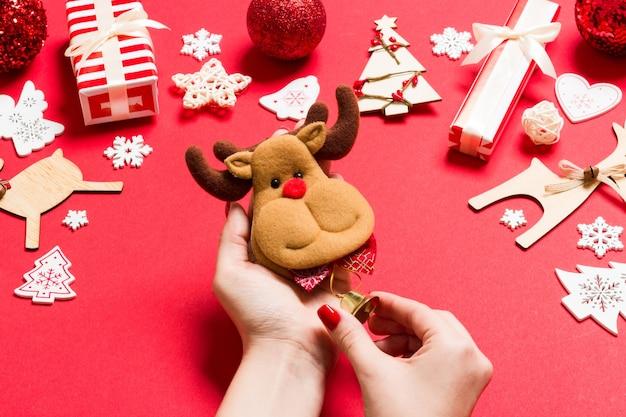 빨간색 배경에 여성 손에 순록의 상위 뷰. 크리스마스 장식들. 새 해 휴일 개념