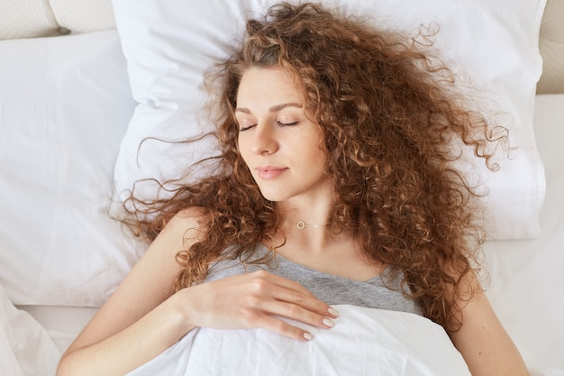 リラックスした巻き毛の女性の平面図はベッドで健康的な睡眠をとり、白いリネンの上に横たわり、夜は心地よい夢を楽しんでいます。
