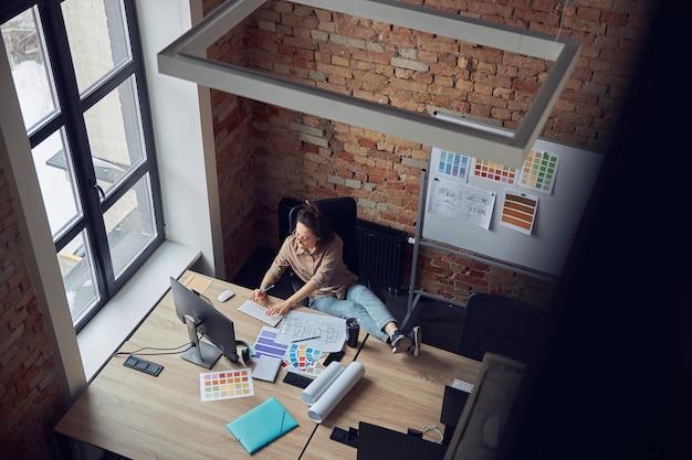 새로운 인테리어 디자인 프로젝트를 진행하는 동안 타이핑을 하는 편안한 여성 디자이너의 상위 뷰