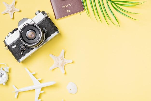 노란색 표면에 레트로 카메라, 장난감 비행기, 여권, 불가사리 및 알람 시계의 상위 뷰