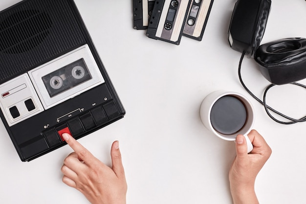 Взгляд сверху ретро магнитофона, кассет и наушников лежа на белой поверхности.