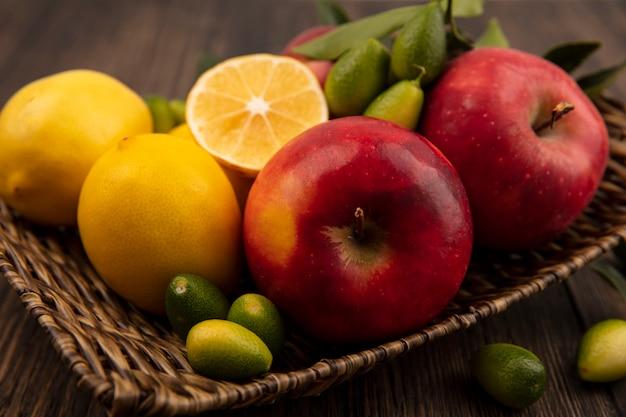 나무 표면에 고리 버들 쟁반에 사과 레몬과 킨칸과 같은 비타민 과일이 풍부한 상위 뷰