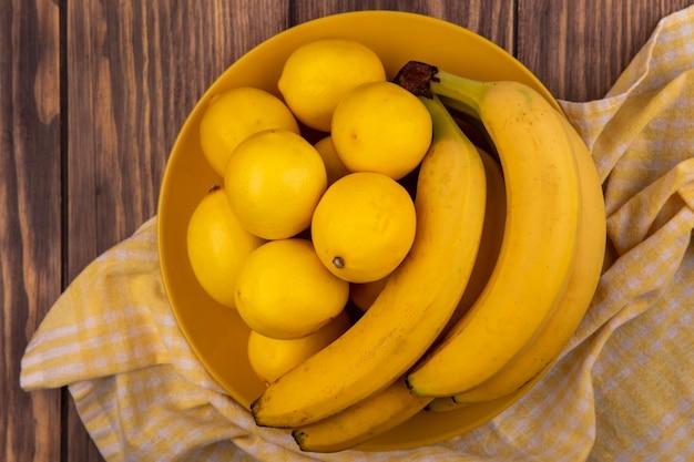 木製の壁にバナナと黄色のチェックの布の上の黄色のプレート上の豊富なビタミンレモンの上面図
