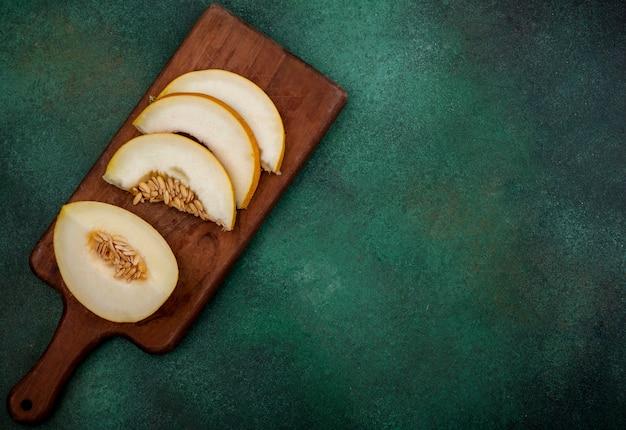 緑の表面に木製キッチンボード上のメロンの熟した、おいしいスライスのトップビュー