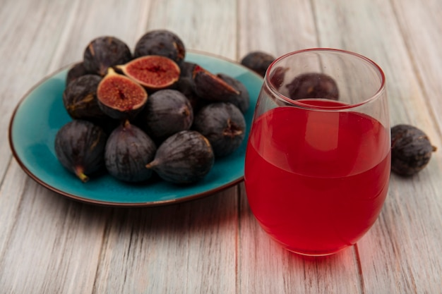 灰色の木製の壁のガラスに新鮮なフルーツジュースと青い皿に熟した黒いミッションイチジクの上面図