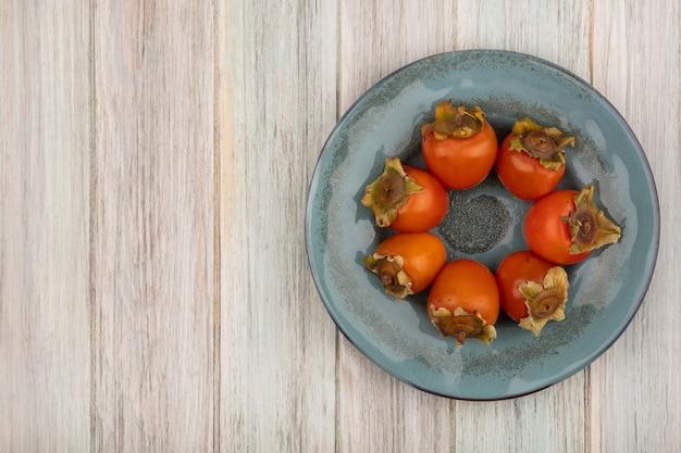 コピースペースと灰色の木製の背景の上のプレート上の熟した新鮮な柿の上面図