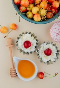 Вид сверху спелой дождливой вишни в миску с творогом в мини-пирог банках и медом на белом